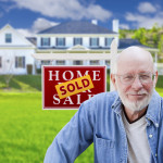 Senior posing in front of home for sale sign
