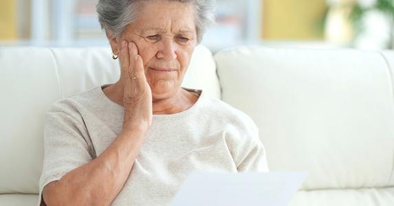 upset-elderly-woman-reading-letter